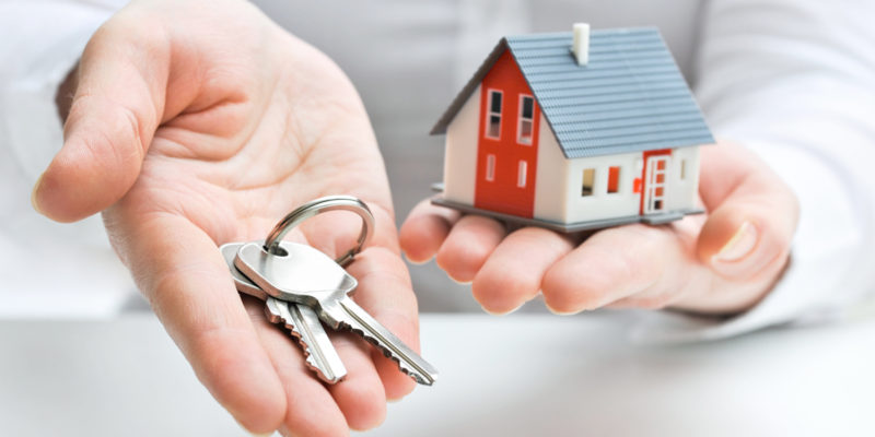 Person holding model house and keys