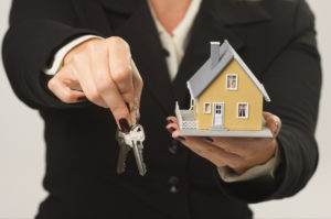 Female Realtor presenting keys and small house.